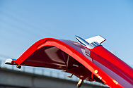 Bellmore, NY, USA. August 24, 2018. Closeup of rocket ornaments on open hood of red 1957 Chevy Bel Air that is on display at Bellmore Friday Night Car Show, in parking lot of LIRR Bellmore station.