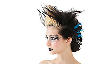 Close-up of beautiful gothic woman with spiked hair and face painting over white background