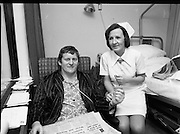 Barry  McGann, Rugby International   (K81)..1977..13.01.1977..01.13.1977..13th January 1977..Following a training ground accident at the 'Ireland Team Trial' Barry McGann was admitted to St Vincents Nursing Home, Merrion Road, Dublin, for treatment and recuperation..Picture of Nurse Carmel Houlihan from Cork taking the pulse of Barry McGann in St Vincents Nursing Home.