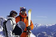 Male skier and female snowboarder stand on mountain taking in the view