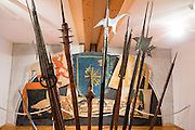 The Appenzell Museum displays hand and long shaft weapons (halberd and flail type) from the 1500s-1600s. Behind are 1640-1663 replicas (by painter Hans Bildstein) of flags captured from the 1403-1407 Appenzell Wars of Liberation, through the wars against the Turks around 1600, which were kept in the parish church until 1822 as offerings to God and St. Mauritius. Appenzell Museum, which is in the town hall, shows a cross section of the Swiss Canton's history and culture. Appenzell village is in Appenzell Innerrhoden, Switzerland's most traditional and smallest-population canton (second smallest by area).