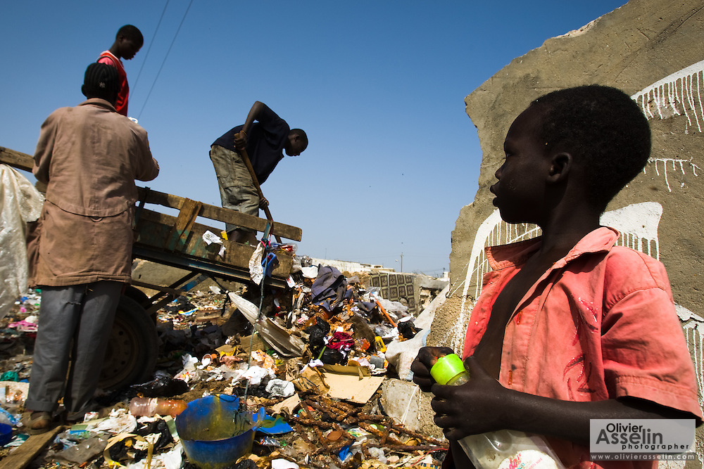 A boy watches while older boys unload a horse-pulled cart loaded with garbage into a home that was damaged by flooding in the Medina Gounass neighborhood of Guediawaye, Senegal on  Friday May 1, 2009. (Olivier Asselin for the New York Times).
