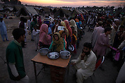 People displaced by the floods line up for food distribution at a camp in Sukkur, in Sindh Province, Pakistan.