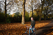 In Utrecht rijden fietsers langs het Julianapark waar de bomen mooie herfstkleuren hebben.<br /> <br /> In Utrecht cyclists pass the Juliana park with trees in autumn colors.