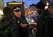 Police Sergeant explains to young black men why they have been stopped and searched. Forest Gate area of Newham East London in the days following the murder of 15 year old Stephen Lewis. Operation Blunt 2.  Monday 26th January 2009.<br />