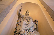 Statue of Pallas Athena holding a spear, in a niche inside the Brandenburg Gate or Brandenburger Tor, 18th century, a neoclassical triumphal arch marking one of the old city gates of Berlin, at the end of Unter den Linden, Berlin, Germany. The gate was commissioned by King Frederick William II of Prussia as a sign of peace and built by Carl Gotthard Langhans 1788-91. It stood inaccessible next to the Berlin Wall during Germany's Partition and was restored 2000-02 by the Stiftung Denkmalschutz Berlin. It consists of 12 Doric columns and is topped by a statue of a quadriga, a chariot pulled by 4 horses. Picture by Manuel Cohen