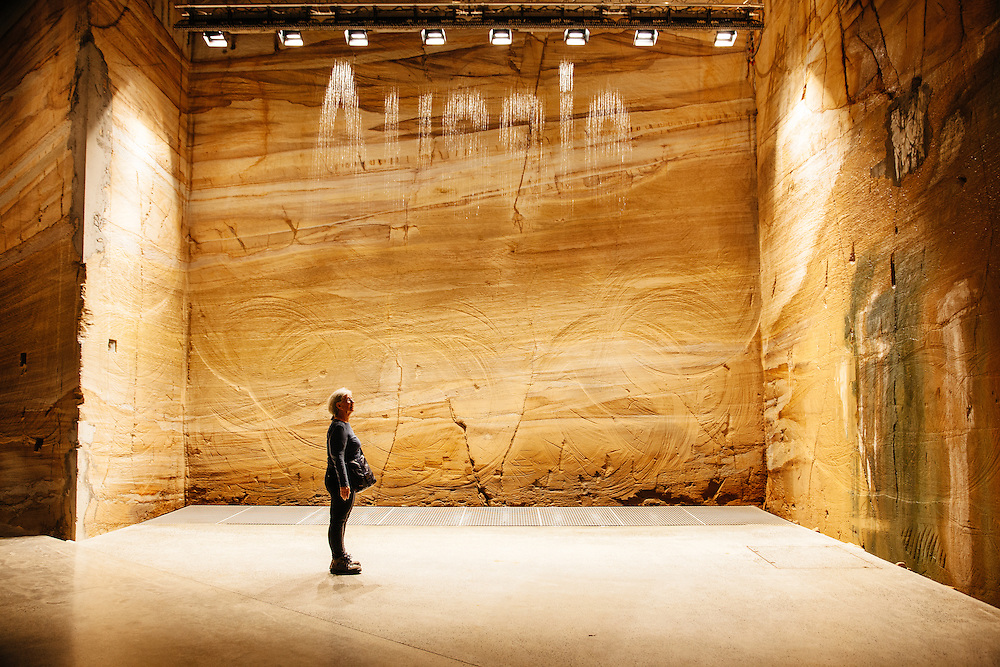 A single female figure stands in front of an installation which randomly generates words from falling water at the Museum of Old and New Art (MONA) in Hobart.