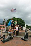 """Annapolis, Maryland - June 05, 2016: Siblings Maia, 8, and Adham Eissa, 9, right, eat ice cream with their friend Christopher, left, (parents don't want his last name published) atop the Kunta Kinte-Alex Haley Memorial statue in historic Annapolis Sunday June 5th, 2016. Earlier that day a perigean spring tide brought some of the highest water levels of the year to the coastal town and partially flooded the park. <br /> <br /> A perigean spring tide brings nuisance flooding to Annapolis, Md. These phenomena -- colloquially know as a """"King Tides"""" -- happen three to four times a year and create the highest tides for coastal areas, except when storms aren't a factor. Annapolis is extremely susceptible to nuisance flooding anyway, but the amount of nuisance flooding has skyrocketed in the last ten years. Scientists point to climate change for this uptick. <br /> <br /> <br /> CREDIT: Matt Roth for The New York Times<br /> Assignment ID: 30191272A"""