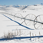 farm irregation equipment lies idle in the snowy field in Idaho