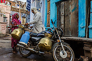 A woman comes down the street from her home to buy some milk from the milkman, who stopped his bike in a street corner.