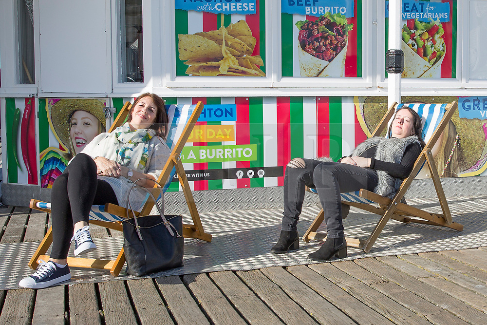 © Licensed to London News Pictures. 17/02/2018. Brighton, UK. Members of the public relax in the sunshine on the beach and Brighton Palace Pier as sunny and milder weather is hitting the seaside resort. Photo credit: Hugo Michiels/LNP