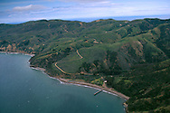 Aerial over green hills above the coast and water near Prisoners Harbor, Santa Cruz Island, Channel Islands, California
