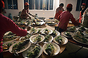 "A jeans factory prepares fish as part of a banquet for its workers and executives to celebrate Chinese New Year in Zhongshan city, China. .This picture is part of a photo and text story on blue jeans production in China by Justin Jin. .China, the ""factory of the world"", is now also the major producer for blue jeans. To meet production demand, thousands of workers sweat through the night scrubbing, spraying and tearing trousers to create their rugged look. .At dawn, workers bundle the garment off to another factory for packaging and shipping around the world..The workers are among the 200 million migrant labourers criss-crossing China.looking for a better life, at the same time building their country into a.mighty industrial power."
