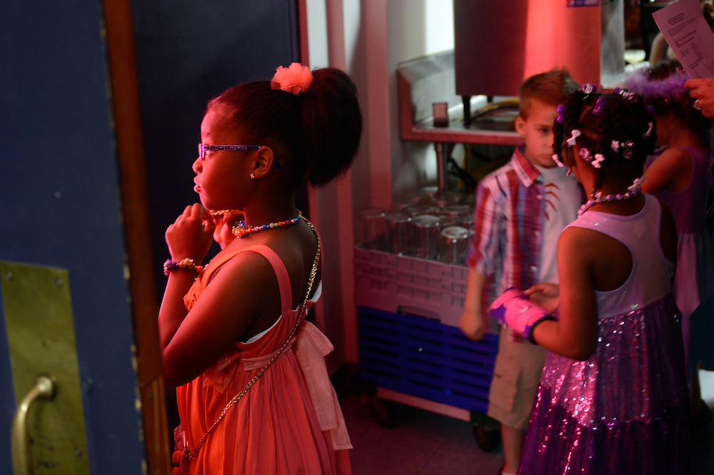 Mariah Stuckey, 7, waits calmly in the glow of light from the stage as she waits Thursday to make her entrance as a model in the annual Easter Seals Auxiliary fashion show at Par-A-Dice hotel in East Peoria.