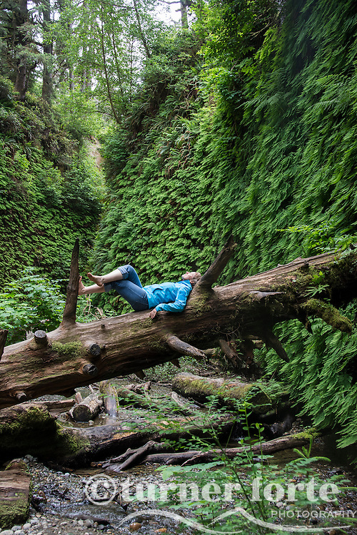 Woman lays on back on fallen tree trunk and views canyon walls, Fern Canyon, Prarie Creek Redwoods State Park, Redwood National Park, California.
