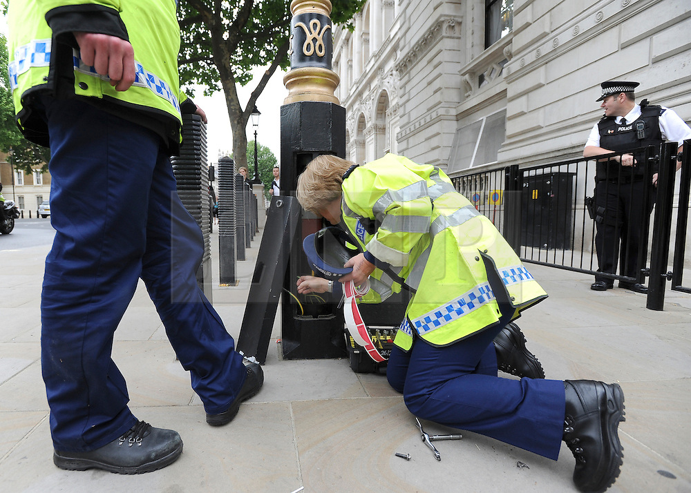 © under license to London News Pictures. LONDON, UK  17/05/2011. Police officers check a lamp post outside Downing Street before placing a security seal on it. Police carry out security checks in Whitehall, Central London today (17 May 2011). Please see special instructions for usage rates. Photo credit should read Stephen Simpson/LNP.