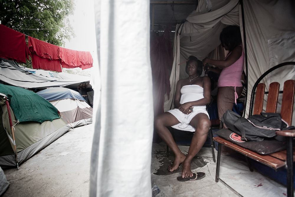 A prostitute has her hair done in a brothel in a one of the tented camps in Port au Prince, Haiti