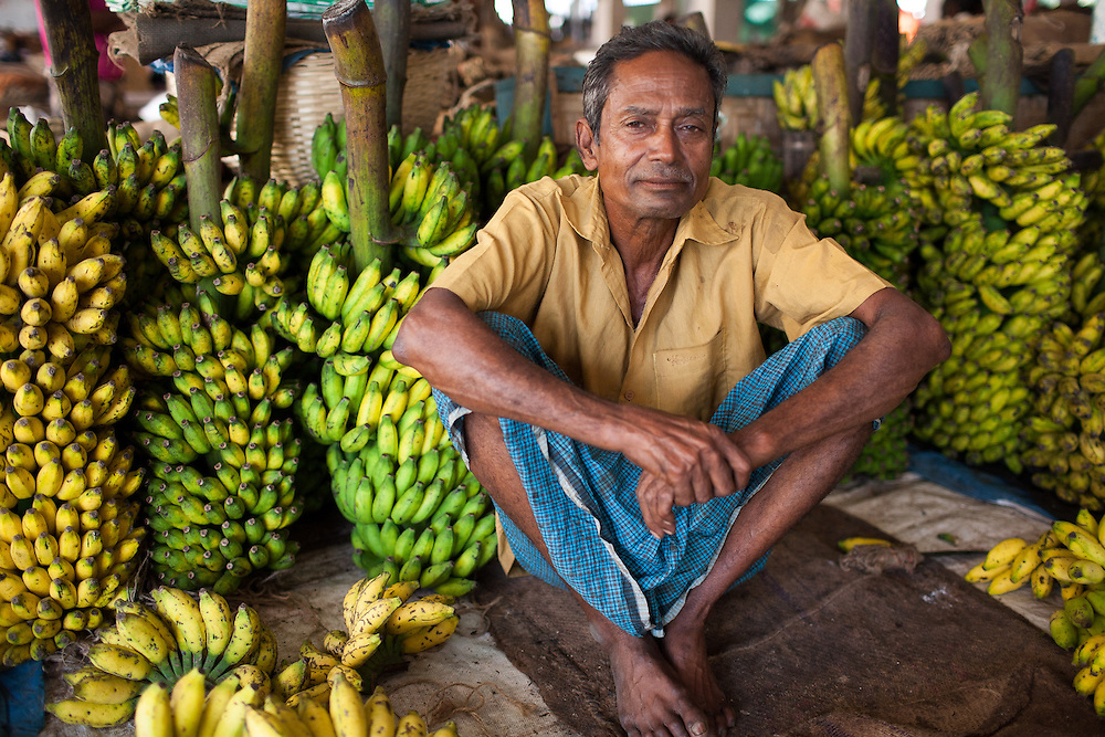 A man sits and waits to sell bananas in the municipal market in Srimongol in the tea growing region of north east Bangladesh