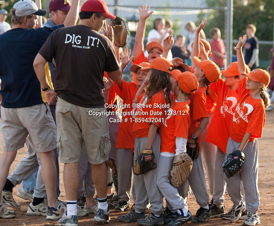 Mixed boys and girls baseball team responding to coaches with raised hands age 7. St Paul Minnesota MN USA