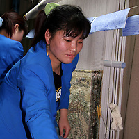 Asia, China, Beijing. Chinese silk carpet weaver.