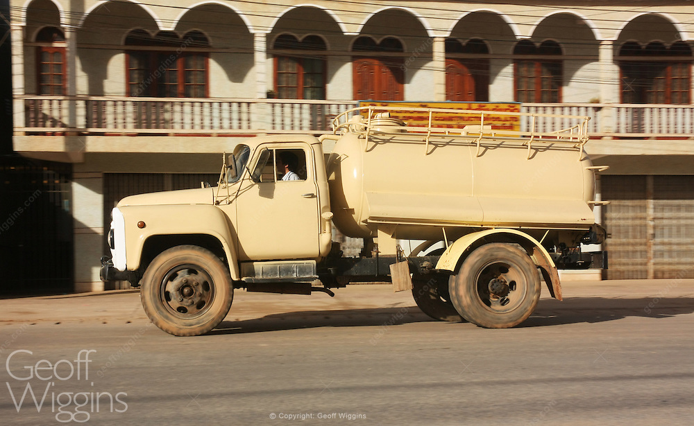 Vintage Russian manufactured GAZ 52 tanker truck races through Laotian street