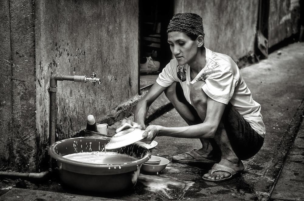Washing dishes in Klong Toey, Bangkok, Thailand. PHOTO BY LEE CRAKER