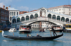 Gondolier and his gondola on the Grand Canal at Rialto Bridge in Venice Italy
