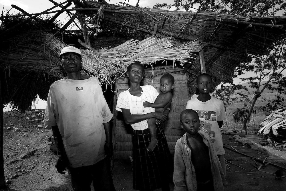 A family stands in front of their home.