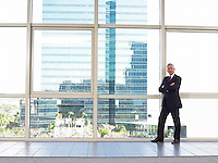 Businessman by window in office building portrait
