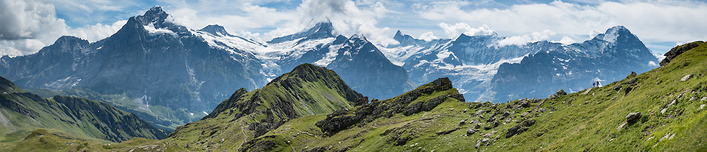 Seen from upper Bussalp, Wetterhorn, Schreckhorn, Finsteraarhorn and Eiger (left to right) rise impressively above Grindelwald, in Switzerland, the Alps, Europe. The Finsteraarhorn (at left 4274 m / 14,022 ft) is the highest mountain in the Bernese Alps and the most prominent peak of Switzerland (in terms of height above the lowest topographic contour at the mountain's base). The Schreckhorn (4078 m / 13,379 ft) is the northernmost summit rising above 4000 meters in Europe. On the right, the north face of the Eiger rises to 3970 m (13,020 ft). This whole massif and surrounding glaciers were designated as part of UNESCO's Jungfrau-Aletsch World Heritage Site. This image was stitched from multiple overlapping photos.