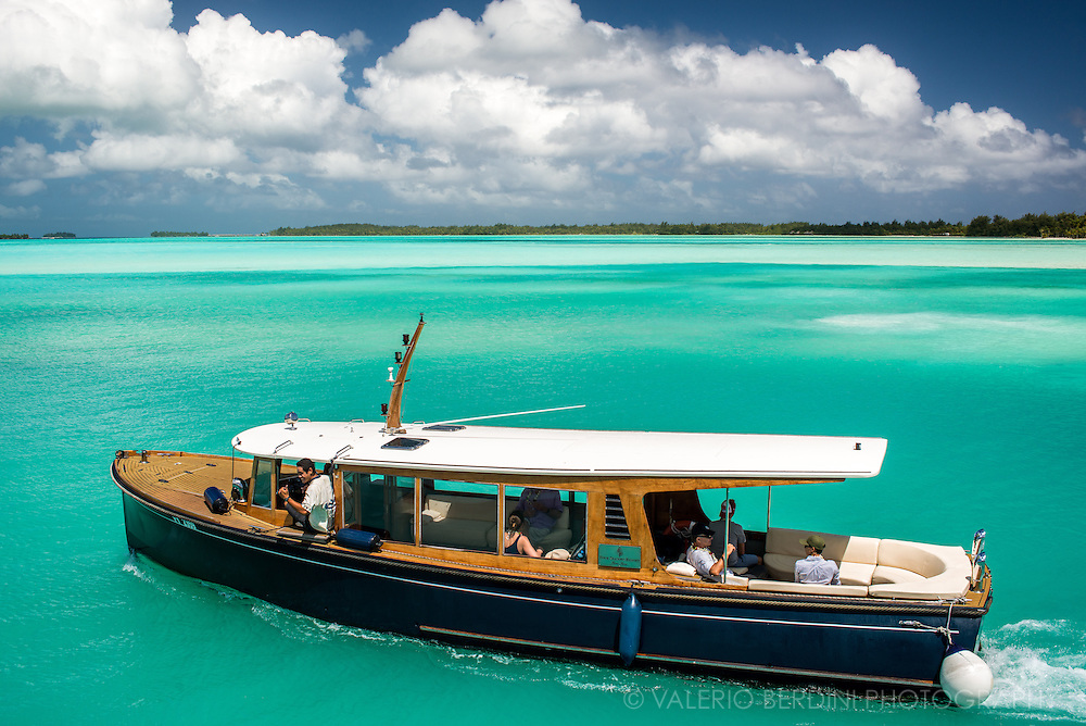 A private boat crosses the lagoon to take tourists to Four Seasons luxury resorts in Bora Bora.