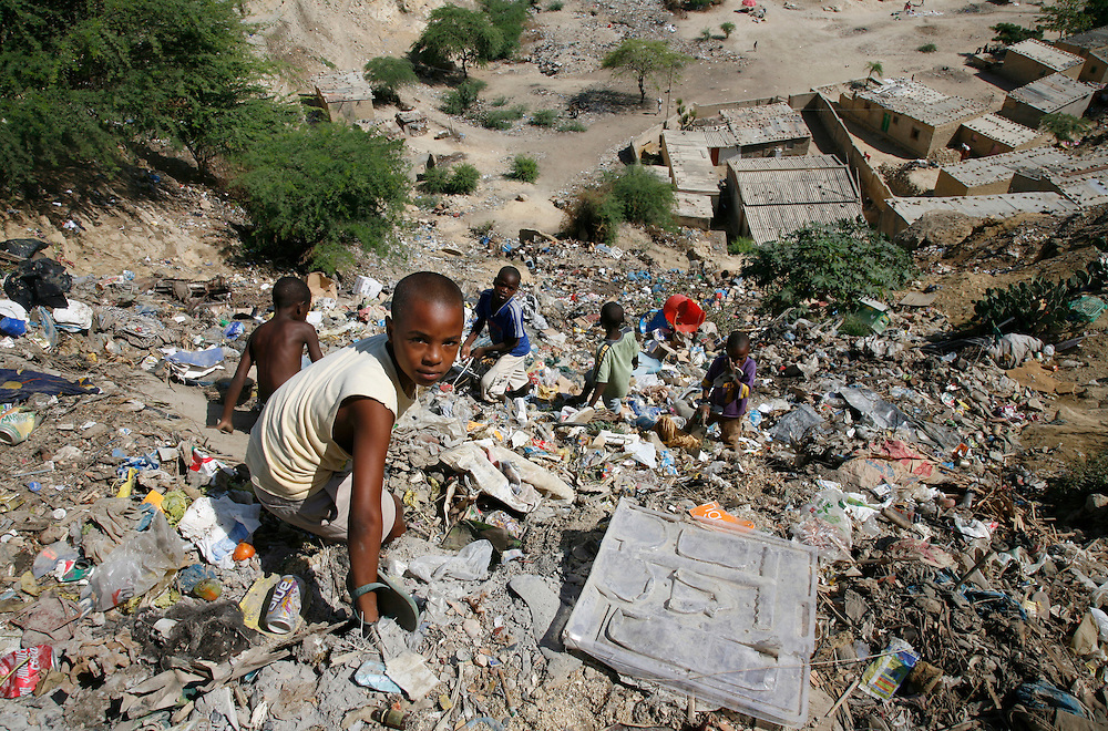 Children climbing down steep slope of rubbish just outside their home. Bairro area on the hills north of Lobito. Benguela Province. Angola. Africa. .Pictures © Z & D Lightfoot..www.lightfootphoto.co.uk