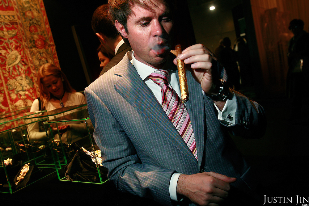German entrepreuneur Matthias Wintzer smokes a gold-wrapped cigar at the Millionaire Fair in Moscow. Wintzer sells the cigars for USD100 each. .Millionaires, billionaires and those who bought 1,000-rouble tickets were among the thousands who visited the fair held in the Crocus city expo centre. .The four-day event, held for the second year in a row, ended on October 30. The products on sale include a diamond-studded mobile phone worth a million dollars, an island, latest sports cars and other items that might appeal to the growing millionaire market..Twenty years ago, there were no official millionaires in the whole of Russia. Now Moscow has 25 billionaires and the country has 88,000 millionaires, according to Forbes Magazine. ..