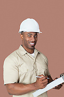 Portrait of happy young African male construction worker holding clipboard over brown background