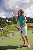 Girl, 14, enjoys a round of mini-golf at the Adventure Zone, Blackcomb Mountain, Whistler, BC Canada.