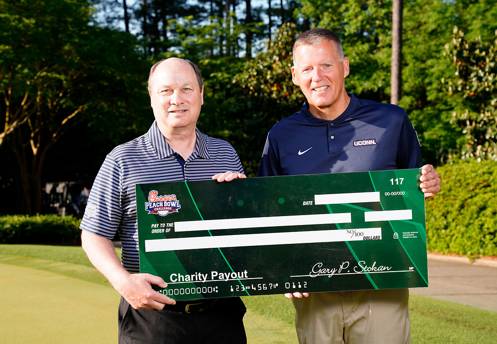 Peach Bowl, Inc. CEO & President Gary Stokan presents Uconn head football coach Randy Edsall a check for his charity after the Chick-fil-A Peach Bowl Challenge at the Ritz Carlton Reynolds, Lake Oconee, on Tuesday, April 30, 2019, in Greensboro, GA. (Paul Abell via Abell Images for Chick-fil-A Peach Bowl Challenge)