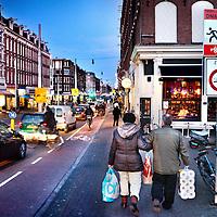 Nederland, Amsterdam , 13 december 2011..De economische recessie 2011 wordt langzamerhand zichtbaar..Op de foto winkelend stelletje met toiletpapier loopt door de Kinkerstraat ter hoogte van de Bilderdijkstraat..Foto:Jean-Pierre Jans