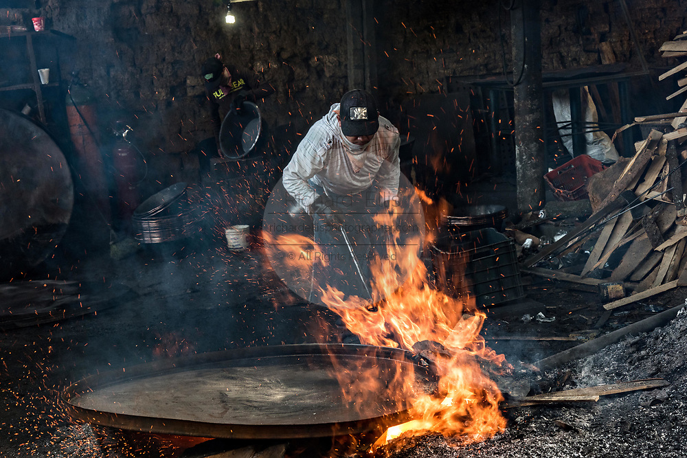 An indigenous Purepecha worker places a copper pan on an open forge to begin the process of hardening and forming the pan at a copper workshop in Santa Clara del Cobre, Michoacan, Mexico. The Purepecha people have been crafting copper crafts since the 12th century.