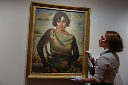 "© Licensed to London News Pictures. 21/04/2017. London, UK.  A staff member views ""Portrait de Madame Batanouni Bey"", 1923, by Mahmoud Said, (est. GBP 150-250k), at a preview at Sotheby's, New Bond Street, of upcoming sales of Arts of the Islamic World, 20th century Middle East Art and Orientalist art. Photo credit : Stephen Chung/LNP"