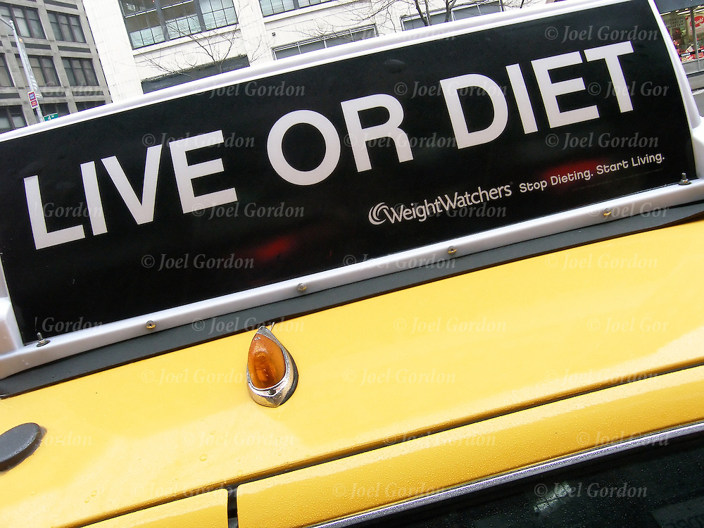 "Advertising sign on top to NYC cab, ""Live or Diet"", WeightWatchers stop dieting and start living"