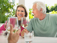 Three people sitting at verandah holding wine glasses