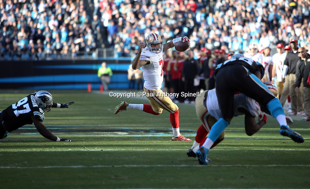 San Francisco 49ers quarterback Colin Kaepernick (7) avoids a tackle attempt by Carolina Panthers defensive end Mario Addison (97) as he runs the ball on a keeper in the fourth quarter during the NFC Divisional Playoff NFL football game against the Carolina Panthers on Sunday, Jan. 12, 2014 in Charlotte, N.C. The 49ers won the game 23-10. ©Paul Anthony Spinelli