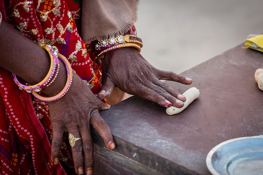 A woman rolls some dough in the morning near Jal Mahal