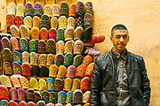 FEZ, MOROCCO 2ND FEBRUARY 2018 - Portrait of a market vendor selling colourful babouches and tailor made Moroccan shoes at his market stall in the old Fez Medina, Middle Atlas Mountains, Morocco.