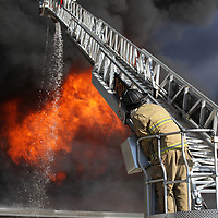 A Pontotoc fireman redirects the water flow from the ladder truck as fight a massive fire at American Furniture in Ecru on Friday.