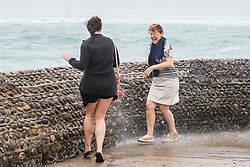 © Licensed to London News Pictures. 25/06/2017. Brighton, UK. members of the public are being drenched by powerful waves hitting the pontoon on Brighton and Hove beach. Photo credit: Hugo Michiels/LNP