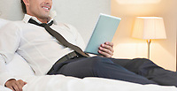 Mature businessman lying on bed while using digital tablet at home