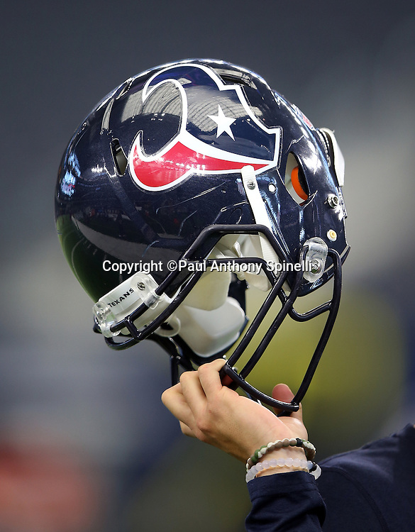 An assistant holds up a Houston Texans helmet during the 2015 NFL preseason football game against the Dallas Cowboys on Thursday, Sept. 3, 2015 in Arlington, Texas. The Cowboys won the game 21-14. (©Paul Anthony Spinelli)