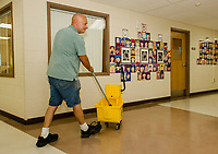 """James Moussette applies one of the six layers of wax to the floors at Elm Street School in preparation for the """"first day"""" September 4th in the Laconia School District.  (Karen Bobotas/for the Laconia Daily Sun)"""