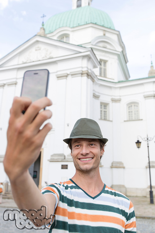 Young man taking self portrait outside St. Casimir Church; Warsaw; Poland